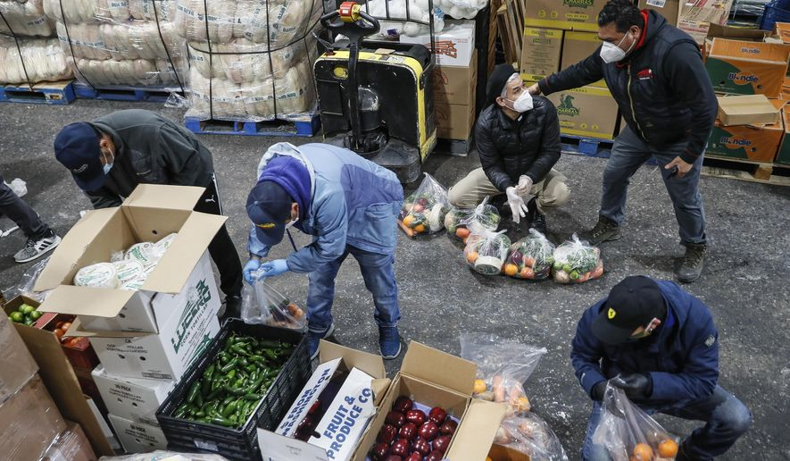 Fabian Arias, a Lutheran pastor with St. Peter's Church in Manhattan, center right, coordinates with volunteers as they prepare food delivery donations at a produce wholesaler, Friday, May 8, 2020, in the Bronx borough of New York. (AP Photo/John Minchillo, File)