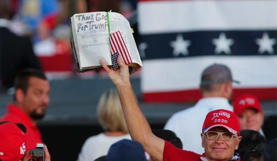 A Trump supporter lifts a Bible at a President Donald Trump campaign rally in Gastonia, N.C., Wednesday, Oct. 21, 2020. (AP Photo/Nell Redmond)