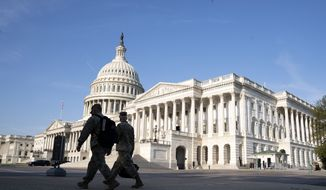 The U.S. Capitol is seen as national guard members pass by on Capitol Hill in Washington, Thursday, May 20, 2021. The House voted to create an independent commission on the deadly Jan. 6 insurrection at the U.S. Capitol, sending the legislation to an uncertain future in the Senate. (AP Photo/Jose Luis Magana)