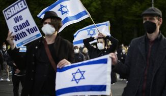 People with Israeli flags attend a rally in support of Israel, in Berlin, Germany, Thursday, May 20, 2021. (AP Photo/Markus Schreiber
