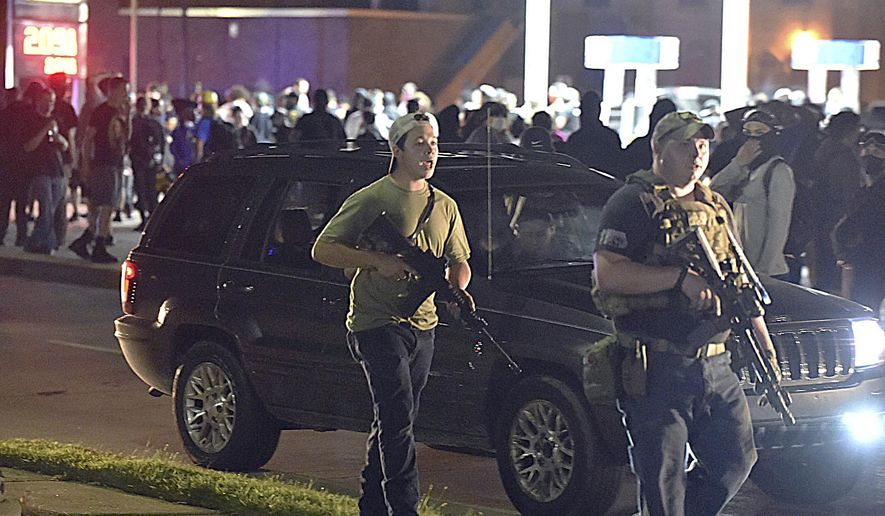 In this Aug. 25, 2020, file photo, Kyle Rittenhouse, left, with backwards cap, walks along Sheridan Road in Kenosha, Wis., with another armed civilian. Rittenhouse, the Illinois man accused of killing two people during the chaotic protests that followed the police shooting of Jacob Blake in Wisconsin, was due Friday, May 21, 2020, to make his first in-person court appearance. COVID-19 protocols in the Kenosha County courthouse have forced Rittenhouse to make all his court appearances since he was charged in August via video from his attorney's office.  (Adam Rogan/The Journal Times via AP, File)