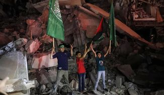 Palestinian children wave green Hamas and their national flags as they stand on the rubble of a destroyed building while celebrating the cease-fire agreement between Israel and Hamas in Gaza City, early Friday, May 21, 2021. (AP Photo/Adel Hana)