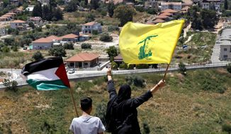 In this May 15, 2021, file photo, Lebanese wave Hezbollah and Palestinian flags, as they stand in front of the Israeli town of Metula, background, on the Lebanese side of the Lebanese-Israeli border in the southern village of Kfar Kila, Lebanon. Lebanon's Hezbollah militia looms large over the current Israel-Hamas war, even though it has stayed out of the fighting so far. Hezbollah's firepower is far greater than that of Gaza's Hamas rulers, and Israel keeps a wary eye on its northern border for any signs Hezbollah might get off the sidelines. (AP Photo/Hussein Malla, File)