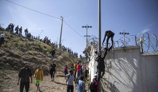In this May 18, 2021, file photo, people climb a fence in the area at the Spain-Morocco border, outside the Spanish enclave of Ceuta. Thousands of would-be migrants converged on the Moroccan border town of Fnideq this week, part of an extraordinary mass effort to swim or scale barbed-wire fences to get into Spain for a chance at a new life. (AP Photo/Mosa'ab Elshamy)