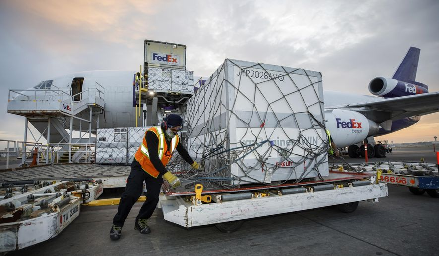 Workers unload a shipment of the Moderna COVID-19 vaccine at the FedEx hub at Pearson International Airport in Toronto on Thursday, May 20, 2021. (Cole Burston/The Canadian Press via AP) ** FILE **