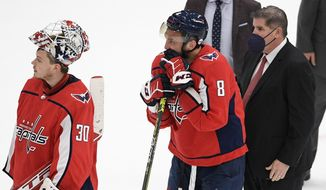 Washington Capitals left wing Alex Ovechkin (8), goaltender Ilya Samsonov (30) and head coach Peter Laviolette stand in the handshake line after Game 5 of an NHL hockey Stanley Cup first-round playoff series against the Boston Bruins, Sunday, May 23, 2021, in Washington. The Bruins won 3-1. (AP Photo/Nick Wass)