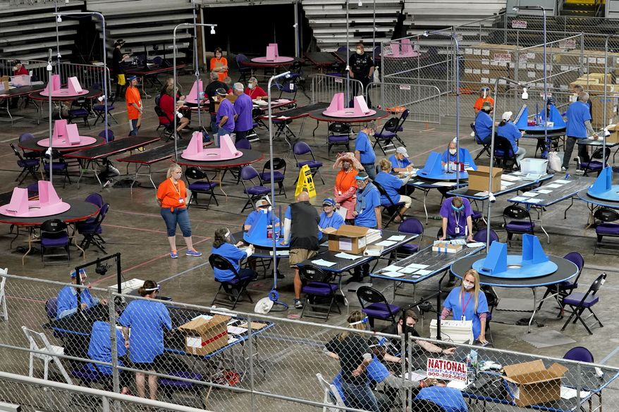 In this May 6, 2021, file photo Maricopa County ballots cast in the 2020 general election are examined and recounted by contractors working for Florida-based company, Cyber Ninjas, at Veterans Memorial Coliseum in Phoenix. Maricopa County officials on Friday, May 21, directed the Arizona Senate and the auditors it hired to review the county's 2020 election count to preserve documents for a possible lawsuit. (AP Photo/Matt York, Pool, File)