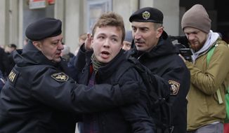 In this Sunday, March 26, 2017, file photo, Belarus police detain journalist Raman Pratasevich, center, in Minsk, Belarus. Raman Pratasevich, a founder of a messaging app channel that has been a key information conduit for opponents of Belarus' authoritarian president, has been arrested after an airliner in which he was riding was diverted to Belarus because of a bomb threat. The presidential press service said President Alexander Lukashenko personally ordered that a MiG-29 fighter jet accompany the Ryanair plane — traveling from Athens, Greece, to Vilnius, Lithuania — to the Minsk airport. (AP Photo/Sergei Grits, File)