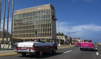 """In this Oct. 3, 2017, file photo, tourists ride classic convertible cars on the Malecon beside the U.S. Embassy in Havana, Cuba. The Biden administration faces increasing pressure to respond to a sharply growing number of reported injuries suffered by diplomats, intelligence officers and military personnel that some suspect are caused by devices that emit waves of energy that disrupt brain function. The problem has been labeled the """"Havana Syndrome,"""" because the first cases affected personnel in 2016 at the U.S. Embassy in Cuba. (AP Photo/Desmond Boylan, File)"""