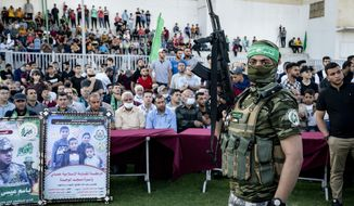 Militants stand guard around the stage as Yahya Sinwar, the Palestinian leader of Hamas in the Gaza Strip, makes an appearance at a rally of supporters days after a cease-fire was reached following an 11-day war between Gaza's Hamas rulers and Israel, Monday, May 24, 2021, in Gaza City, the Gaza Strip. (AP Photo/John Minchillo)