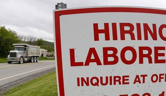 In this file photo from May 5, 2021, a truck passes a sign showing a need to hire laborers outside a concrete products company in Evans City, Pa. Pennsylvania will resume work search requirements in July for hundreds of thousands of people receiving unemployment compensation, a top Wolf administration official said Monday, May 24, 2021. (AP Photo/Keith Srakocic, File)  **FILE**