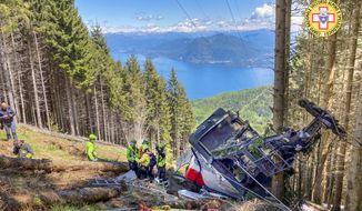 Rescuers work by the wreckage of a cable car after it collapsed near the summit of the Stresa-Mottarone line in the Piedmont region, northern Italy, Sunday, May 23, 2022. A mountaintop cable car plunged to the ground in northern Italy on Sunday, killing at least nine people and sending at least three more to the hospital, authorities said. (Soccorso Alpino e Speleologico Piemontese via AP)