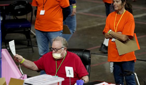 In this May 6, 2021 file photo, Maricopa County ballots cast in the 2020 general election are examined and recounted by contractors working for Florida-based company, Cyber Ninjas at Veterans Memorial Coliseum in Phoenix. (AP Photo/Matt York, Pool)  **FILE**