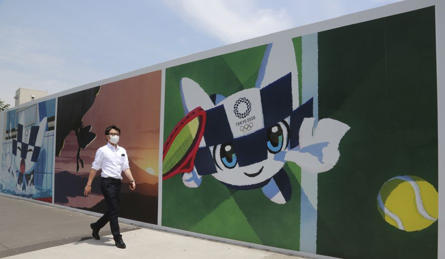 A man walks by posters promoting the Olympic Games planned to start in the summer of 2021, in Tokyo, Monday, May 24, 2021. (AP Photo/Koji Sasahara) **FILE**
