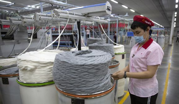 A worker watches as a machine processes cotton yarn at a Huafu Fashion plant, as seen during a government-organized trip for foreign journalists, in Aksu in western China's Xinjiang Uyghur Autonomous Region, Tuesday, April 20, 2021. A backlash against reports of forced labor and other abuses of the largely Muslim Uyghur ethnic group in Xinjiang is taking a toll on China's cotton industry, but it's unclear if the pressure will compel the government or companies to change their ways. (AP Photo/Mark Schiefelbein) ** FILE **