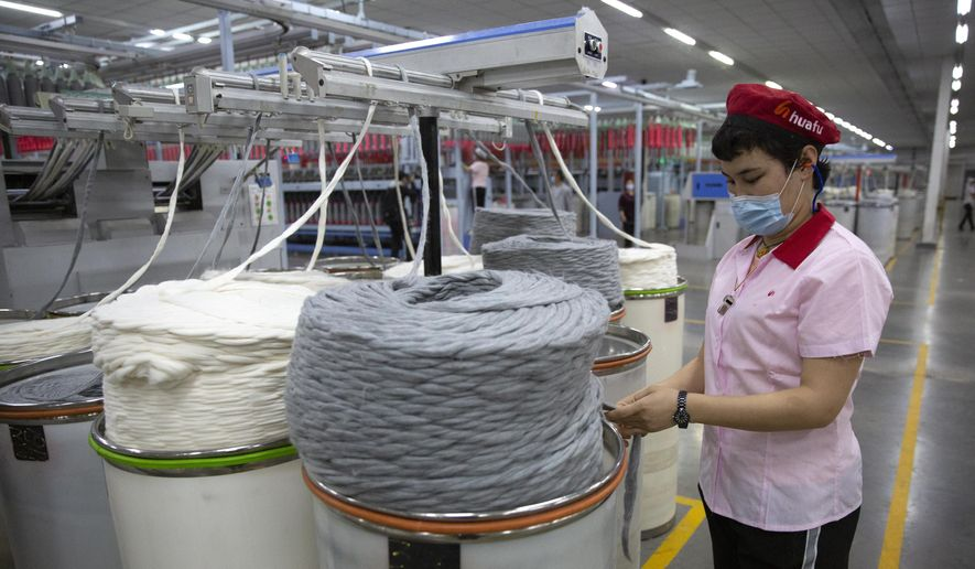 A worker watches as a machine processes cotton yarn at a Huafu Fashion plant, as seen during a government organized trip for foreign journalists, in Aksu in western China's Xinjiang Uyghur Autonomous Region, Tuesday, April 20, 2021. A backlash against reports of forced labor and other abuses of the largely Muslim Uyghur ethnic group in Xinjiang is taking a toll on China's cotton industry, but it's unclear if the pressure will compel the government or companies to change their ways. (AP Photo/Mark Schiefelbein)