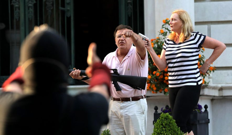 Armed homeowners Mark and Patricia McCloskey, standing in front their house along Portland Place confront protesters marching to St. Louis Mayor Lyda Krewson's house in the Central West End of St. Louis.(Laurie Skrivan/St. Louis Post-Dispatch via AP, File)
