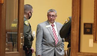 """In this Jan. 12, 2021, file photo, Sen. Anthony Bouchard, R-Cheyenne, chats with Wyoming State Troopers while taking a break during a virtual session of the 66th Wyoming Legislature inside the Senate chamber in Cheyenne, Wyo. Bouchard, a Republican trying to unseat U.S. Rep. Liz Cheney next year, disclosed to supporters in a Facebook Live Video on Thursday, May 20, that he impregnated a 14-year-old girl when he was 18, describing the relationship as """"like the Romeo and Juliet"""" story and saying it was coming to light because of 'dirty politics.' (Michael Cummo/The Wyoming Tribune Eagle via AP, File)  **FILE**"""