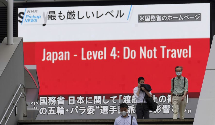 People wearing masks to help protect against the spread of the coronavirus walk in front of a screen showing the news on U.S. warning against visits to Japan Tuesday, May 25, 2021, in Tokyo. U.S. health officials and the State Department on Monday warned Americans against travel to Japan because of a surge in coronavirus cases in the country, which is preparing to host the Olympics in just two months. (AP Photo/Eugene Hoshiko)