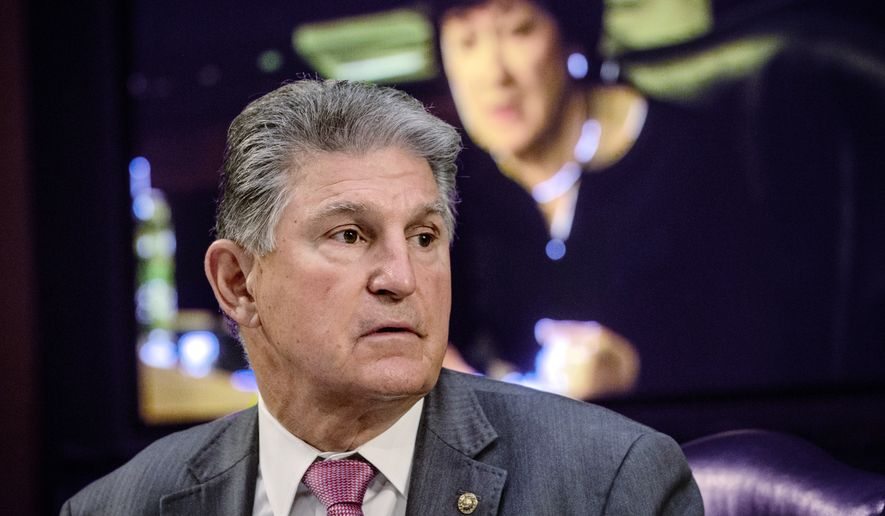 In this May 12, 2021, file photo, Sen. Joe Manchin, D-W.Va., listens as Sen. Susan Collins, R-Maine, on the monitor behind him, asks questions during a hearing on Capitol Hill in Washington. (Bill O'Leary/The Washington Post via AP, Pool) ** FILE **