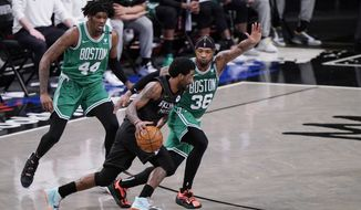 Brooklyn Nets guard Kyrie Irving, center, drives around Boston Celtics guard Marcus Smart (36) as Celtics center Robert Williams III (44) watches during the second quarter of Game 2 of an NBA basketball first-round playoff series Tuesday, May 25, 2021, in New York. (AP Photo/Kathy Willens)