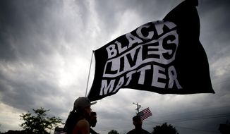 Estephanie Ward, 29, of Flint, Mich., stands alongside other Black Lives Matter supporters waving the flag through the wind as protesters demonstrate along Miller Road outside of a Target, Tuesday, May 25, 2021, in Flint Township, one year after the death of George Floyd. (Jake May/The Flint Journal via AP)