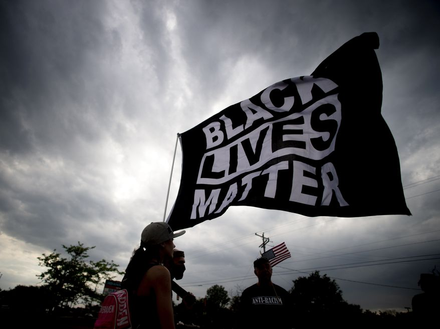 Estephanie Ward, 29, of Flint, Mich., stands alongside other Black Lives Matter supporters waving the flag through the wind as protesters demonstrate along Miller Road outside of a Target, Tuesday, May 25, 2021, in Flint Township, one year after the death of George Floyd. (Jake May/The Flint Journal via AP) ** FILE **