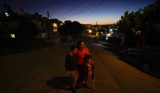 Estela Lazo stands for a portrait with her two children, late Tuesday, Feb. 23, 2021, in Tijuana, Mexico. The Honduran family waits in the Mexican border city to have their case for asylum in the United States heard. As President Joe Biden undoes his predecessor's immigration policies that he considers inhumane, he faces a major question: How far should he go to right perceived wrongs? (AP Photo/Gregory Bull)