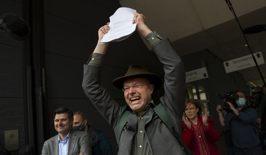 Milieudefensie Director Donald Pols, holding a copy of the verdict, celebrates the outcome in the court case of Milieudefensie, the Dutch arm of the Friends of the Earth environmental organization, against Shell in The Hague, Netherlands, Wednesday, May 26, 2021 In a landmark legal battle of climate change activists in the Netherlands energy giant Shell was ordered to rein in its carbon emissions. (AP Photo/Peter Dejong)