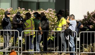 Santa Clara Valley Transportation Authority (VTA) workers gather near a rail yard following a shooting on Wednesday, May 26, 2021, in San Jose, Calif. Santa Clara County sheriff's spokesman said the rail yard shooting left multiple people, including the shooter, dead. (AP Photo/Noah Berger)