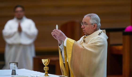 In this Sunday, June 7, 2020, file photo, Archbishop Jose H. Gomez holds a Communion wafer as he celebrates the Solemnity of the Most Holy Trinity, a Mass, with churchgoers present at the Cathedral of Our Lady of the Angels in downtown Los Angeles. The U.S. Conference of Catholic Bishops plans to devote part of its national meeting in June 2021 to the sensitive issue of which Catholics are worthy of receiving Communion. (AP Photo/Damian Dovarganes, File)
