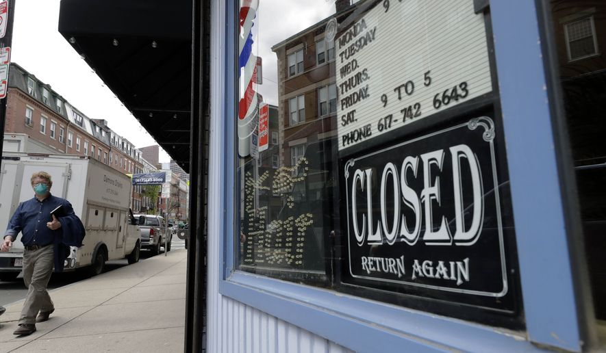 In this May 12, 2020, photo, a pedestrian passes a closed barbershop during the coronavirus pandemic, in the North End neighborhood of Boston. Many small-business owners took on debt to weather the coronavirus pandemic, which forced lockdowns and decimated revenues for large sectors of the economy. Now, those business owners are faced with repaying this debt and rebuilding their companies.  (AP Photo/Steven Senne) **FILE**