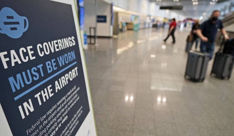 A sign requiring masks is displayed as travelers move about at Cleveland Hopkins International Airport, Wednesday, May 26, 2021, in Cleveland. (AP Photo/Tony Dejak) ** FILE **