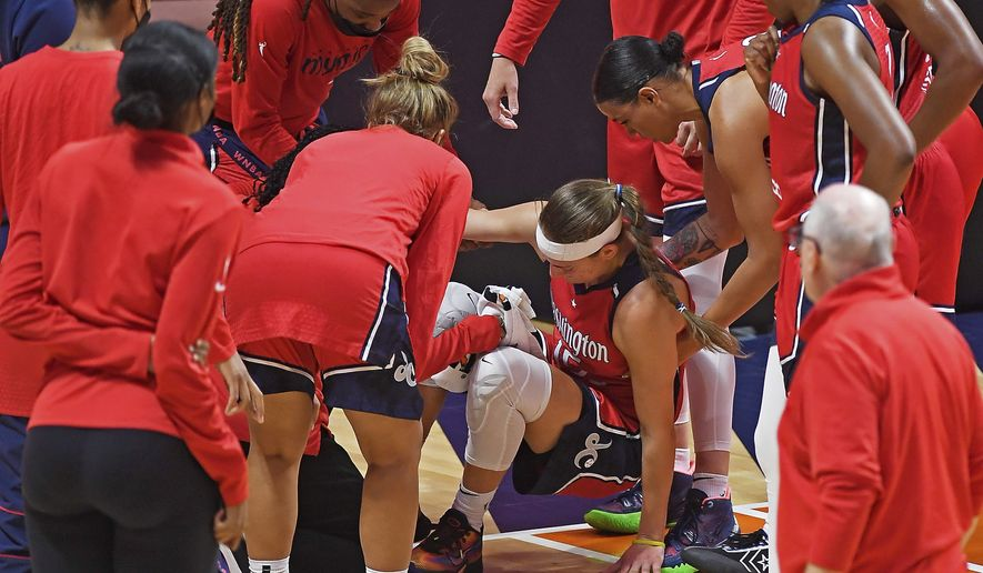 Washington Mystics players check on Sydney Wiese after she went down with an injury during the team's WNBA basketball game against the Connecticut Sun Friday, May 28, 2021, in Uncasville, Conn. (Sean D. Elliot/The Day via AP)