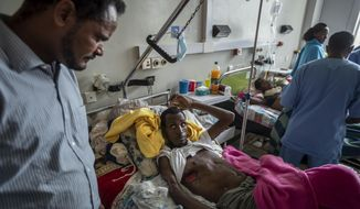 """Farmer Teklemariam Gebremichael, 40, who said he was shot by Eritrean forces in Enticho six months ago and is still recovering, speaks to a doctor, left, at the Ayder Referral Hospital in Mekele, in the Tigray region of northern Ethiopia, on Thursday, May 6, 2021. For months, both Ethiopia and Eritrea denied the presence of Eritrean soldiers in Tigray but Ethiopia's Prime Minister Abiy Ahmed later acknowledged in March that Eritrean troops were """"causing damages to our people."""" (AP Photo/Ben Curtis)"""