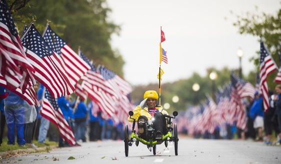 A hand cyclist at the 2015 Marine Corps Marathon in Washington D.C. zips through a mile with fallen veterans honored by wear blue: run to remember. (Photo by Ingrid Barrentine. used with permission)