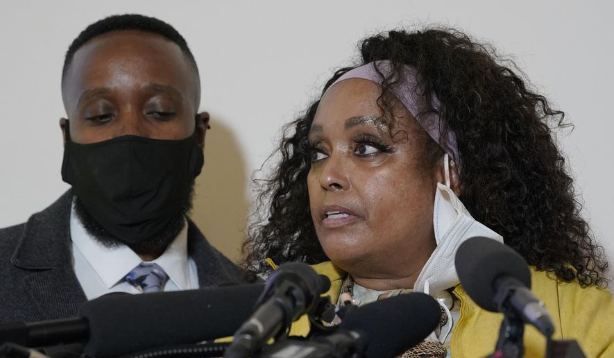 """Marcia Carter-Patterson, right, the mother of Manuel """"Manny"""" Ellis, stands with her son and Ellis' brother Matthew, left, as she speaks Thursday, May 27, 2021, at a news conference in Tacoma, Wash., south of Seattle. Ellis died on March 3, 2020, after he was restrained by police officers. Earlier on Thursday, the Washington state attorney general filed criminal charges against three police officers in the death of Ellis. (AP Photo/Ted S. Warren)"""