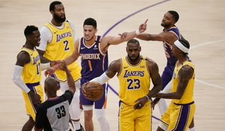 Phoenix Suns guard Devin Booker (1) argues with a referee after fouling Los Angeles Lakers forward LeBron James (23) during the first half in Game 3 of an NBA basketball first-round playoff series Thursday, May 27, 2021, in Los Angeles. (AP Photo/Marcio Jose Sanchez)
