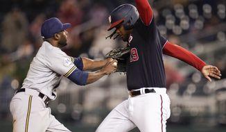 Milwaukee Brewers center fielder Lorenzo Cain, left, tags out Washington Nationals' Josh Bell on a fielder's choice ball hit by Trea Turner during the fourth inning in the second baseball game of a doubleheader, Saturday, May 29, 2021, in Washington. (AP Photo/Julio Cortez)