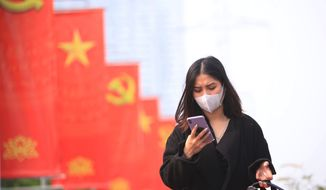 In this Jan. 23, 2021, file photo, a woman wearing a face mask looks at her phone in Hanoi, Vietnam. Vietnam says it has discovered a new coronavirus variant that's a hybrid of strains first found in India and the U.K. The Vietnamese health minister made the announcement Saturday, May 29. (AP Photo/Hau Dinh, File)