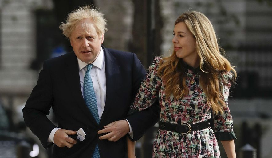 British Prime Minister Boris Johnson arrives at a polling station with his partner Carrie Symonds to cast his vote in local council elections in London.  (AP Photo/Matt Dunham, File)