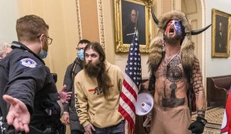 In this Jan. 6, 2021, photo, supporters of President Donald Trump, including Jacob Chansley, right with fur hat, are confronted by U.S. Capitol Police officers outside the Senate Chamber inside the Capitol in Washington. Many of those who stormed the Capitol on Jan. 6 cited falsehoods about the election, and now some of them are hoping their gullibility helps them in court. Albert Watkins, the St. Louis attorney representing Chansley, the so-called QAnon shaman, likened the process to brainwashing, or falling into the clutches of a cult. Repeated exposure to falsehood and incendiary rhetoric, Watkins said, ultimately overwhelmed his client's ability to discern reality. (AP Photo/Manuel Balce Ceneta) **FILE**