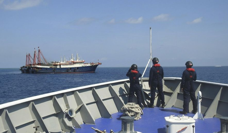In this April 27, 2021, photo provided by the Philippine Coast Guard, its personnel patrol beside ships said to be Chinese militia vessels at Sabina Shoal in the South China Sea. The Philippine government has protested the Chinese coast guard's harassment of Philippine coast guard ships patrolling a disputed shoal in the South China Sea, the Department of Foreign Affairs said Monday, May 3. (Philippine Coast Guard via AP)