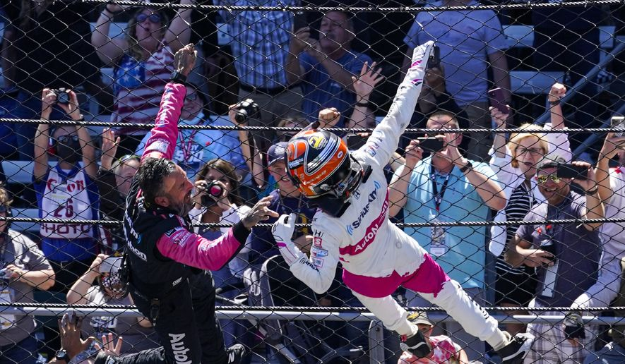 Helio Castroneves, right, of Brazil, celebrates after winning the Indianapolis 500 auto race at Indianapolis Motor Speedway in Indianapolis, Sunday, May 30, 2021. (AP Photo/Darron Cummings)