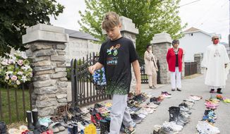 Jamieson Kane puts down tobacco as a tribute to all the victims of the residential school system as he walks among children's shoes outside St. Francis Xavier Church in Kahnawake, Quebec, Sunday, May 30, 2021. (Graham Hughes/The Canadian Press via AP)