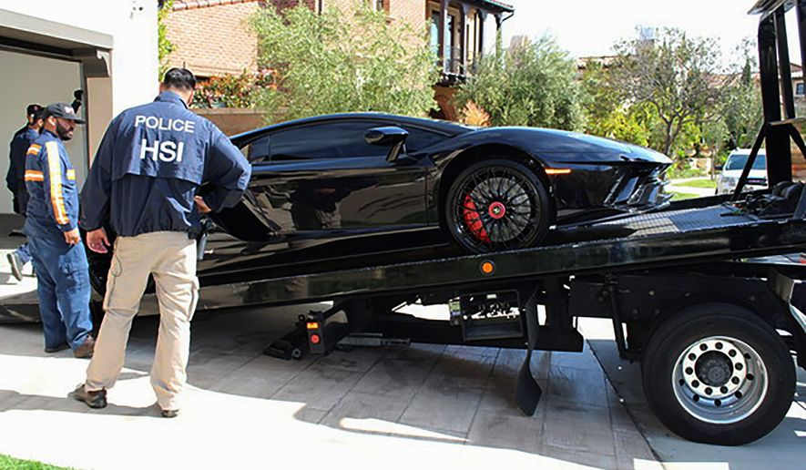 This photo provided by U.S. Immigration and Customs Enforcement shows special agents with HSI Los Angeles's El Camino Real Financial Crimes Task Force seize a Lamborghini from an Orange County businessman on Thursday, April 6, 2021, in Irvine, Calif. (U.S. Immigration and Customs Enforcement via AP) ** FILE **