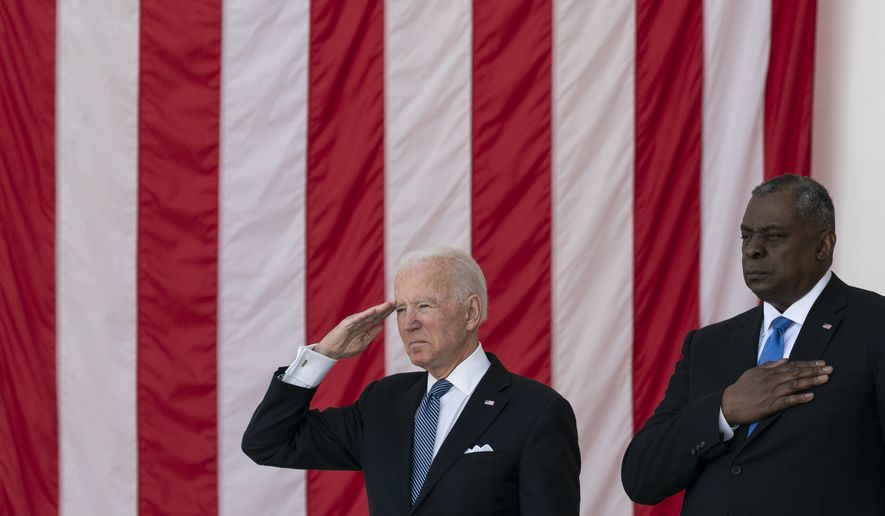 """President Joe Biden salutes as Secretary of Defense Lloyd Austin places his hand over heart during the playing of """"Taps,"""" during the National Memorial Day Observance at the Memorial Amphitheater in Arlington National Cemetery, Monday, May 31, 2021, in Arlington, Va.(AP Photo/Alex Brandon)"""