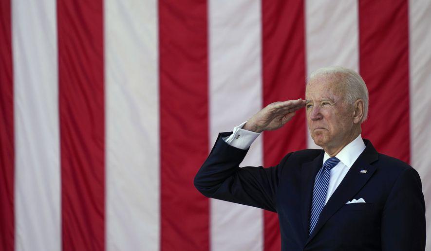 President Joe Biden salutes before speaking during the National Memorial Day Observance at the Memorial Amphitheater in Arlington National Cemetery, Monday, May 31, 2021, in Arlington, Va.(AP Photo/Alex Brandon)
