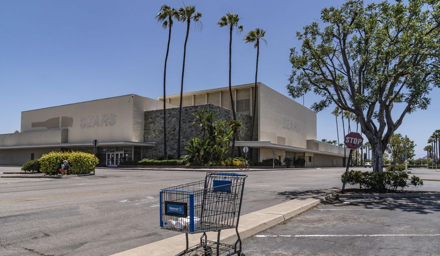 This Thursday, May 27, 2021, photo shows an empty shopping cart in an empty parking lot at the closed Sears in Buena Park Mall in Buena Park, Calif. (AP Photo/Damian Dovarganes)