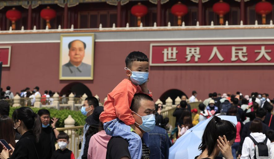 In this May 3, 2021, file photo, a man and child wearing masks visit Tiananmen Gate near the portrait of Mao Zedong in Beijing. China's ruling Communist Party is looking at allowing easing birth limits further to allow couples to have three children instead of two in response to the population's rising age, a state news agency said Monday, May 31, 2021. (AP Photo/Ng Han Guan, File)